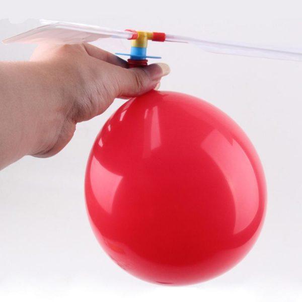 Luftballon Helikopter mit rotem Luftballon in einer Hand