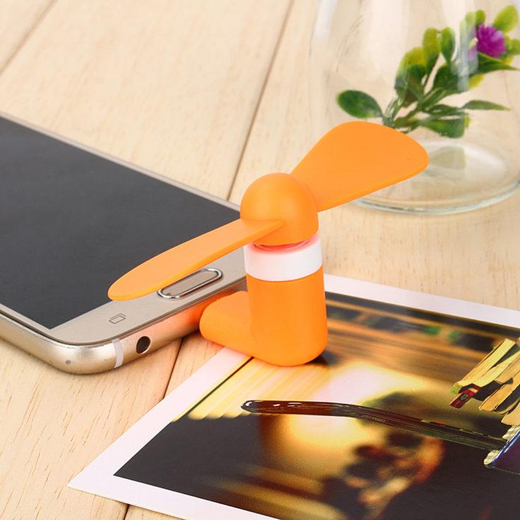 Oranger Smartphone Ventilator an Handy auf einem Tisch.