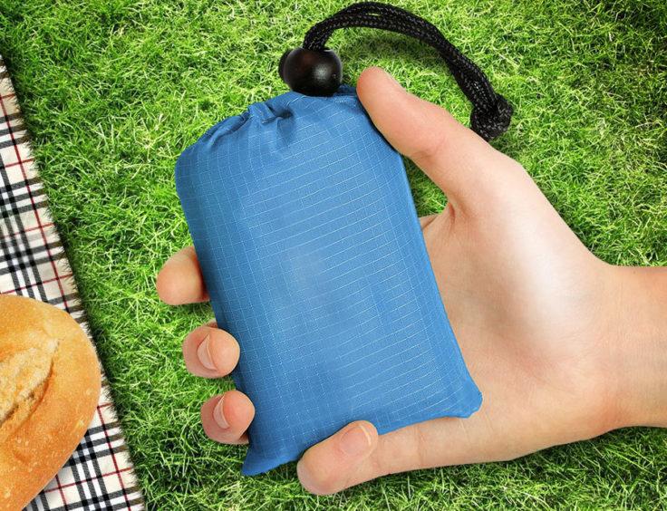 Faltbare Picknickdecke in Blau in einer Hand