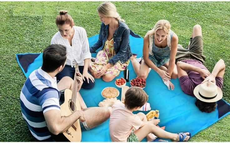 Faltbare Picknickdecke mit Personen auf einer Wiese