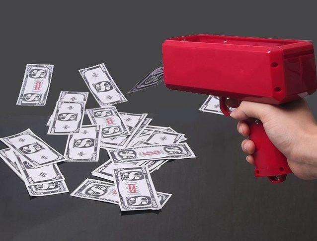 Jemand schießt mit der Money Gun Geldscheine auf den Boden