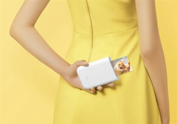 Mi Pocket Photo Printer gehalten von Frau in gelben Kleid